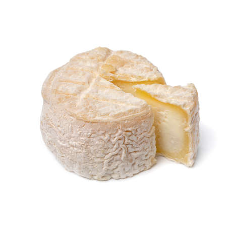 Single whole French small goat cheese with a piece isolated on white background Фото со стока