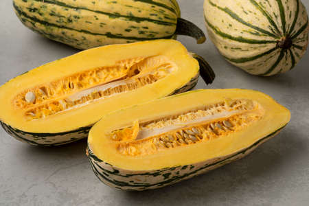 Striped whole Delicata pumkins and halved ones with seeds close up
