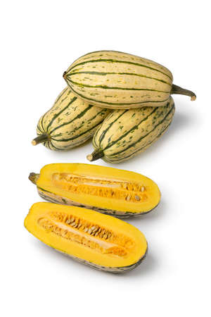 Striped whole Delicata pumkins and halved ones with seeds isolated on white background