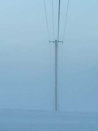 electric power lines on a foggy day Stock Photo