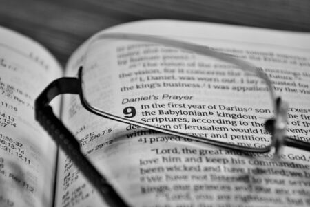 glasses sitting on a bible black and white Stockfoto
