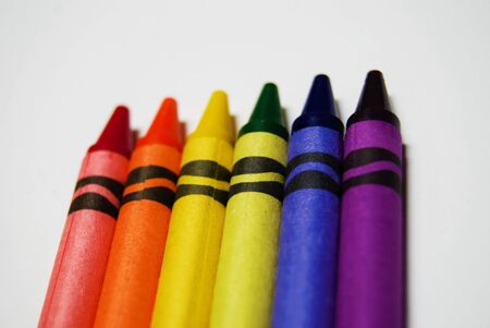 Multi color coloring crayons arranged on a white background