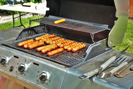hotdogs on the grill at a summertime party
