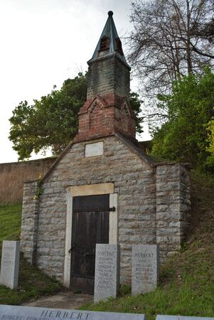 Very old mausoleum built into the side of a hill with steeple, tombstones, and wrought iron fence