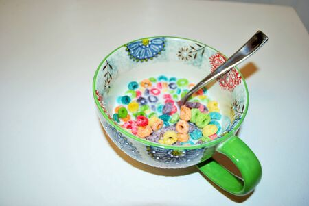 Close up of a bowl full of fruit flavored loops of sugar ready to eat breakfast cereal with a spoon sticking out
