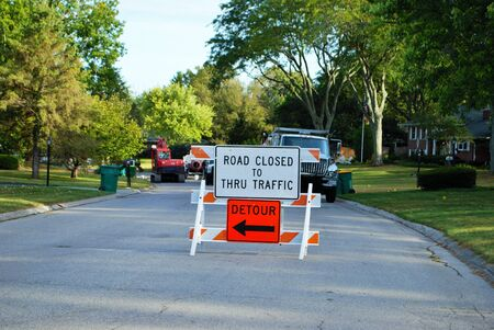 road closed to thru traffic detour construction sign in a residential neighborhood