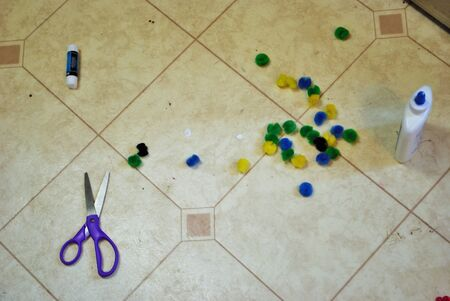 Multi colored cotton balls glue and scissors on a linoleum floor during arts and crafts time