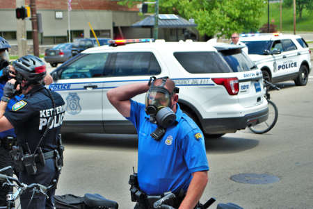 Dayton, Ohio United States 05/30/2020 police officers putting on gas masks preparing to deploy OC pepper spray and tear gas at a black lives matter protest