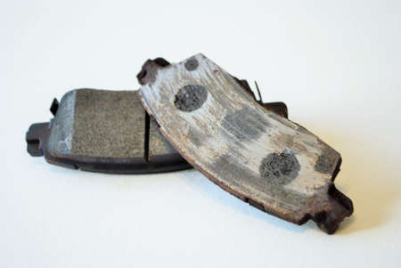 Worn out ruined disc brake pad compared to one that is new Stock Photo