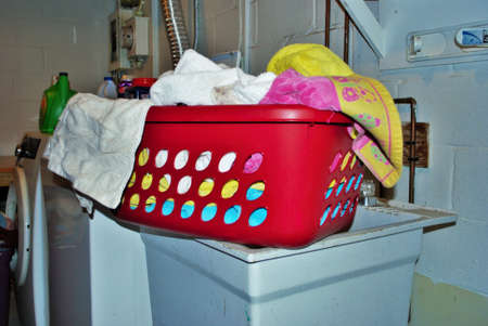 Basket full of dirty towels that need to be washed in a basement laundry room