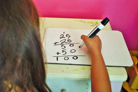 Second grade girl learning how to carry the one on a whiteboard while distance learning not common core math Stock Photo