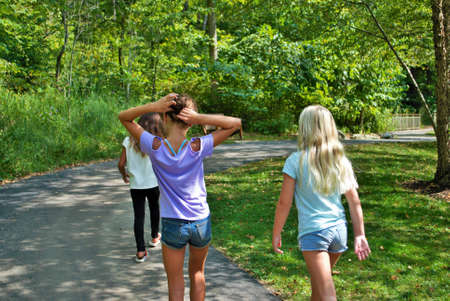 Three little girls taking a hike through the woods