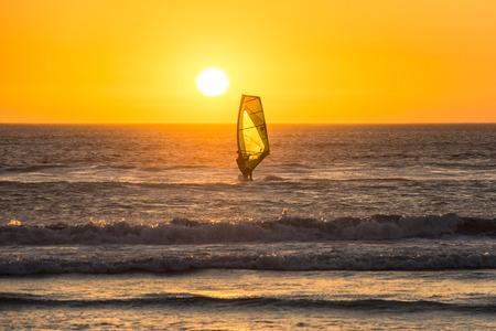 kiteboarding: Kitesurfer surfing in the sunset on beach in Cape Town