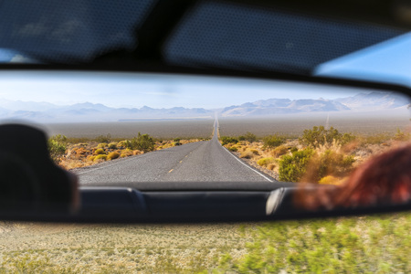 Rear mirror view on desert landscape, Nevada