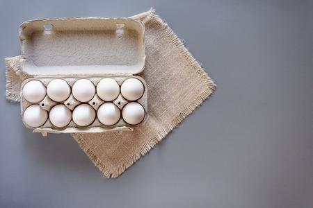 Pappe Eierregal mit Eiern auf grauem Hintergrund. Ansicht von oben. Ländliches Stillleben, natürliches organisches gesundes Lebensmittel mit freiem Raum Standard-Bild - 75725964