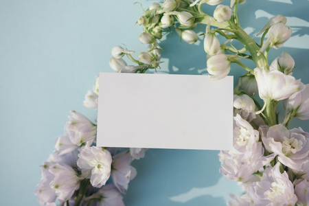 Blank business card mockup with fresh delphinium flowers on pale blue background. 版權商用圖片
