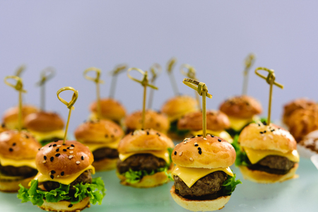 Delicious mini cheeseburgers. Selective focus. Catering for party. Stock Photo