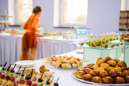 Buffet table of reception with burgers, profiteroles, salads and cold snacs Stock Photo