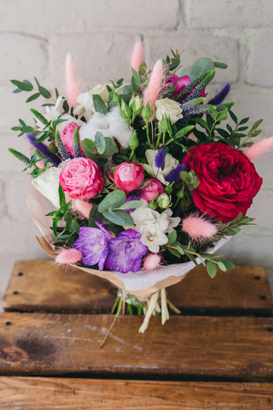 Stylish bouquet of fresh flowers. Composition from freesia, roses, eucalyptus leaves. Close up