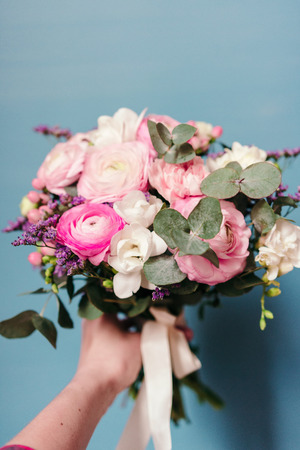 Delicate wedding bouquet of ranunculus flower, freesia and eucalyptus leaves in hand against blue background