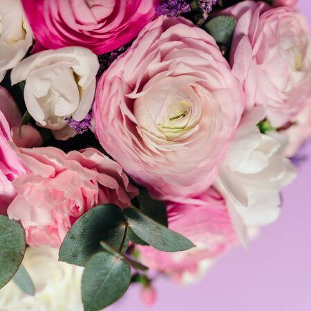 Delicate wedding bouquet of ranunculus flower, freesia and eucalyptus leaves. Close up. Floral background