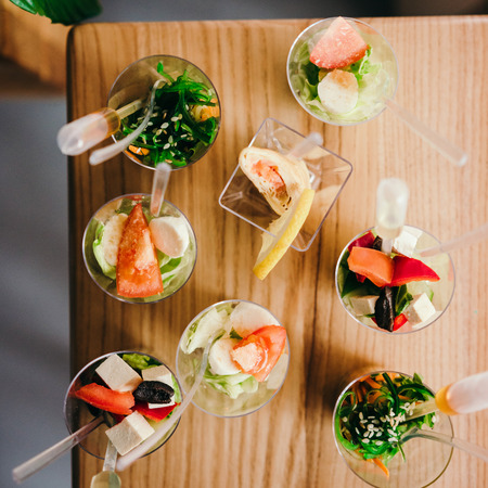 a meeting with a view to marriage: Mini fresh salads with sauce. Top view. Catering - served table with appetizers