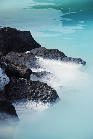 Icelands Blue Lagoon - a close-up of black volcanic lava rocks and blue water