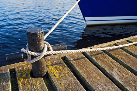 tied in: Close-up of old wooden boat pier and secured cleat rope tied in seamans knot, also the front of the blue boat in the background