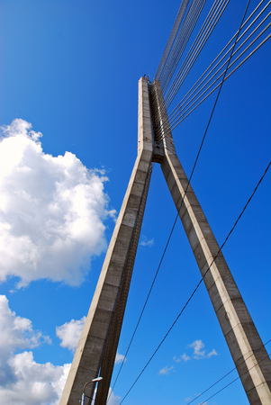 power giant: Cable suspension bridge in Riga, Latvia, close-up of two concrete legs with lined connection metal wires high up in the blue sky, a symbol of power