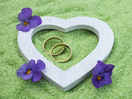 white heart and wedding rings made of wood with delicate blossoms in small stones photo