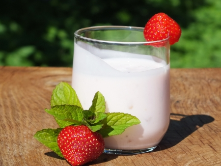 yogurt with fruit on a board made   of oak wood in the garden