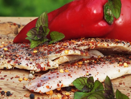 smoked fish with pepper and chili on a bed of oak photo