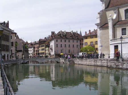 Tourists on the Annecy canal and side view of 12th century  Palais de lIsle surrounding by typical colored houses, pubs and cafes - Annecy, Haute Savoie,France. photo