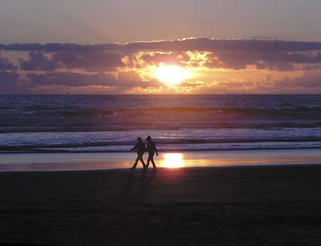Beach lovers walk at sunset at Fort Canby, Washington Imagens