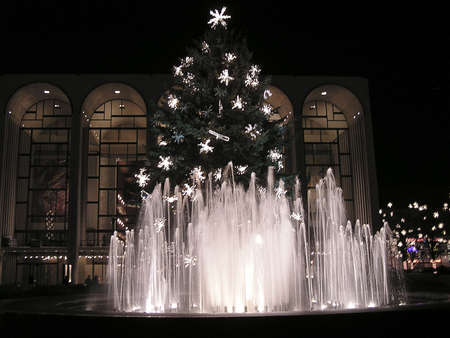 illuminated fountains with Christmas tree decorated with flashing light on night time in New York city, USA Stock Photo
