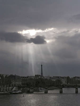 Clouds over Paris bridge and and Eiffel tower from La Seine on a cloudy sundown Imagens