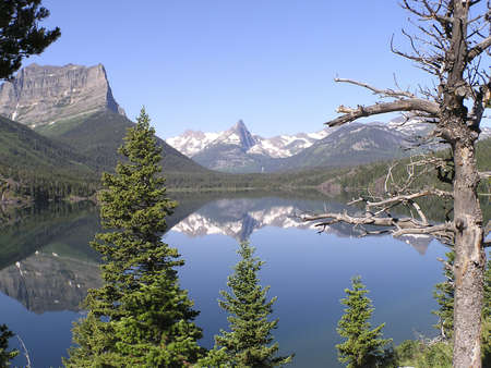 Glaciers peaks reflections on Saint Mary Lake by the hiking trail of of Rising Sun road on East Glacier National Park, Montana, USA
