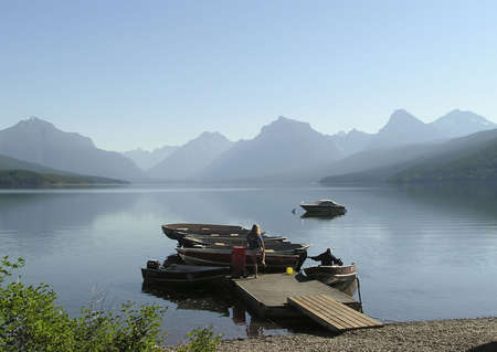 Woman and man on a pier on early morning at lake MacDonald,  West Glacier national Park, Montana Imagens