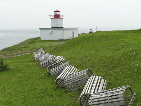 crab pots: lobster traps sitting on the grass  near a lighthouse in New Brunswick harbor, Canada