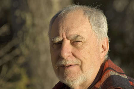 neutral face: Outdoor portrait of a senior man smiling