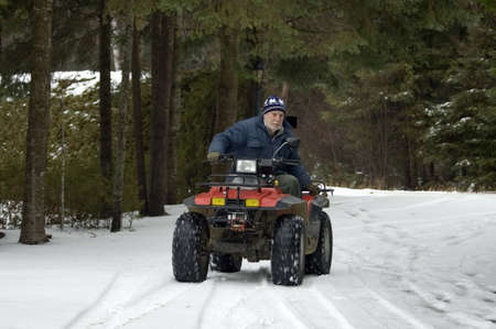 four wheel: Senior male riding a  four wheel ATV over the snow. See the wheels moving.