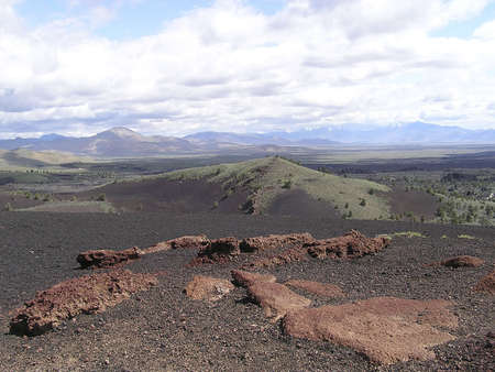 sagebrush: Craters of the Moon national Park, a strange lunar country in  on a cloudy sky, a sea of lava flows with scattered islands of cinder cones ,sagebrush, spatter cones and lava tubes.  Idaho, USA