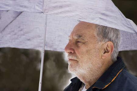 Senior with grey hair holding an umbrella under icy rain