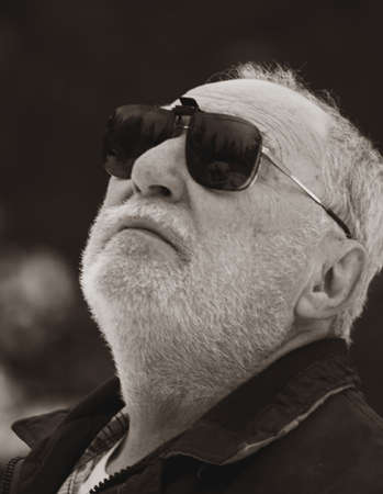 elderly man with his sunglasses looking at the sky Stock Photo