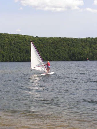 sleek: Senior active woman surfing safely on a lake