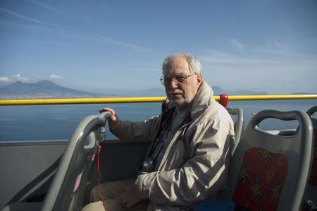 Elderly portrait tourist in a bus tour with the blue sky of Naples in the background Фото со стока - 375056