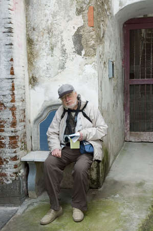 senior tourist relaxing on a bench after a long walk on Amalfi streets in taly Stock Photo