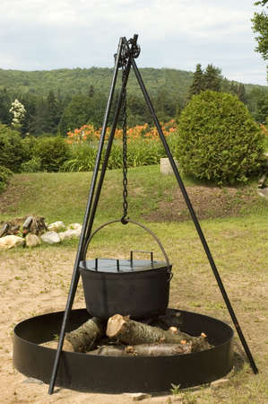Big iron pot ready to cook beans or corns over a campfire on the beach photo