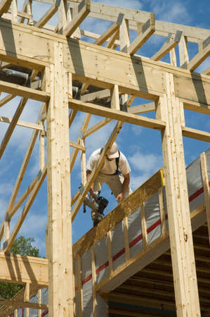 manoeuvre: Construction worker framing the roof of a country house