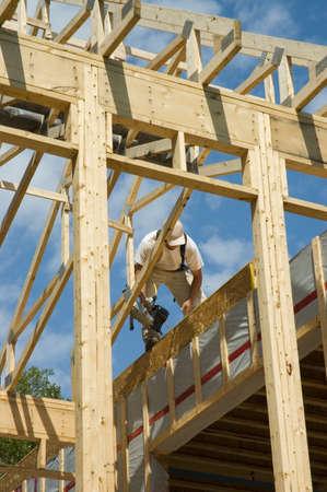 carpintero: Trabajador de la construcci�n enmarcar el tejado de una casa de campo  Foto de archivo